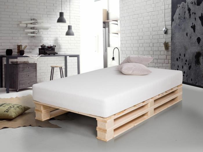 preciosa cama de palets en un ambiente decorado en estilo industrial, paredes de ladrillo, decoración en los tonos del gris