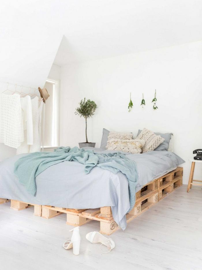 espacioso dormitorio decorado en tonos claros con cama de palets DIY, decoración de plantas verdes