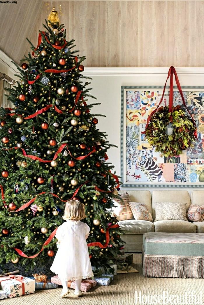 preciosa decoración navideña, grande árbol decorado con adornos en dorado y rojo y cintas de tela rojas