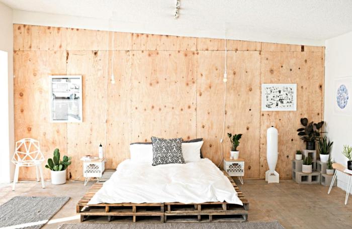 precioso dormitorio con paredes de madera y suelo de parquet, cama de palets grande, decoración de plantas suculentas