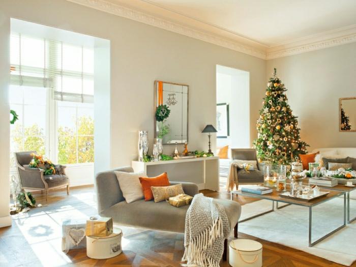 grande salón decorado en estilo moderno en gris con toques en color naranja, bonito árbol de navidad