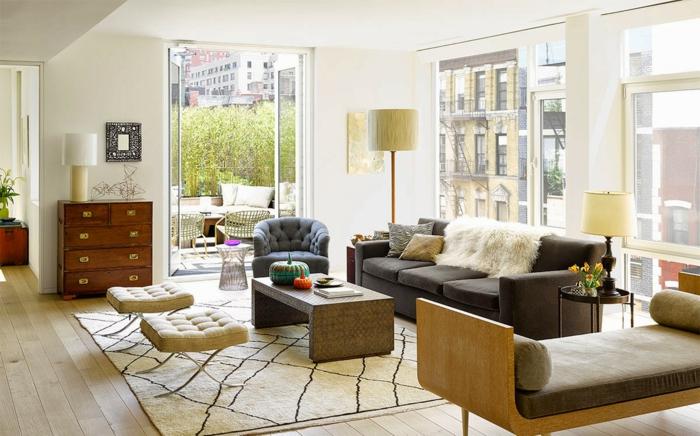 grande salón con ventanales y bonita vista, paredes en color blanco roto, muebles de diseño en gris y beige