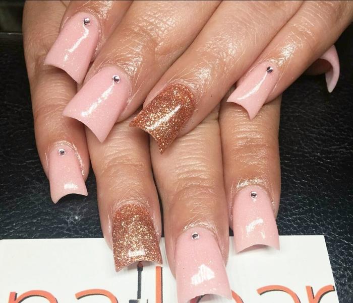 uñas largas de forma cuadrada pintadas en rosado y cobrizo con partículas brillantes, decoracion con piedraas pequeñas