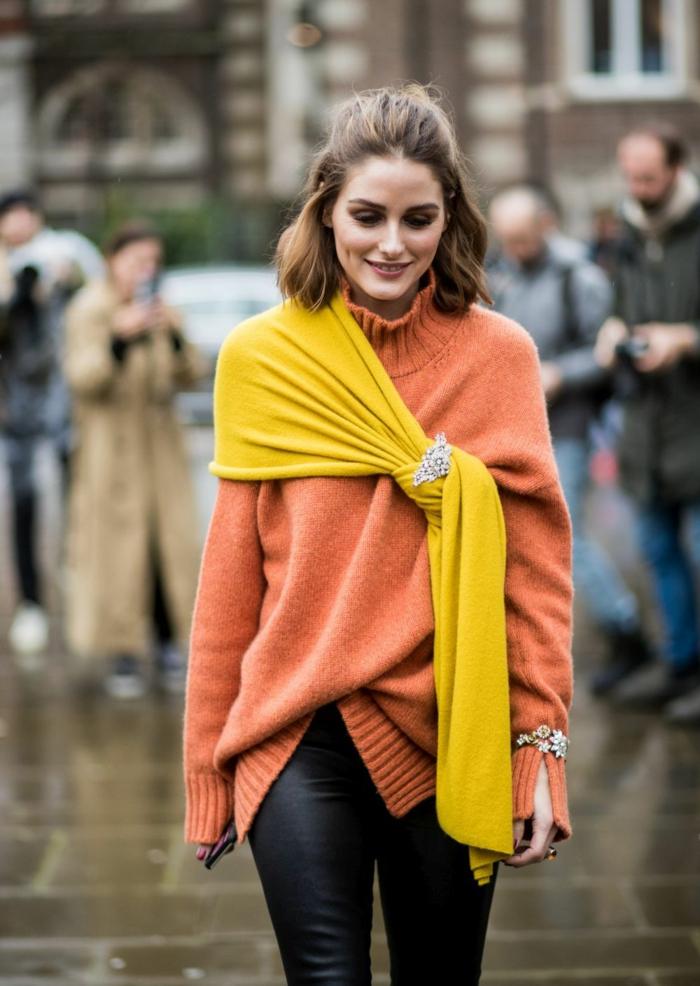 originales formas de ponerse una bufanda o fular, alfombra en color mostaza, vaqueros negros y jersey color naranja