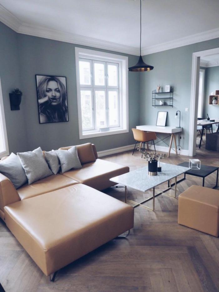 salón con paredes pintadas en color verde menta, sofá en estilo vintage color mostaza, suelo de parquet