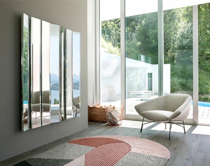 salón moderno con interesantes efectos ópticos, pared pintada en gris con espejo de diseño