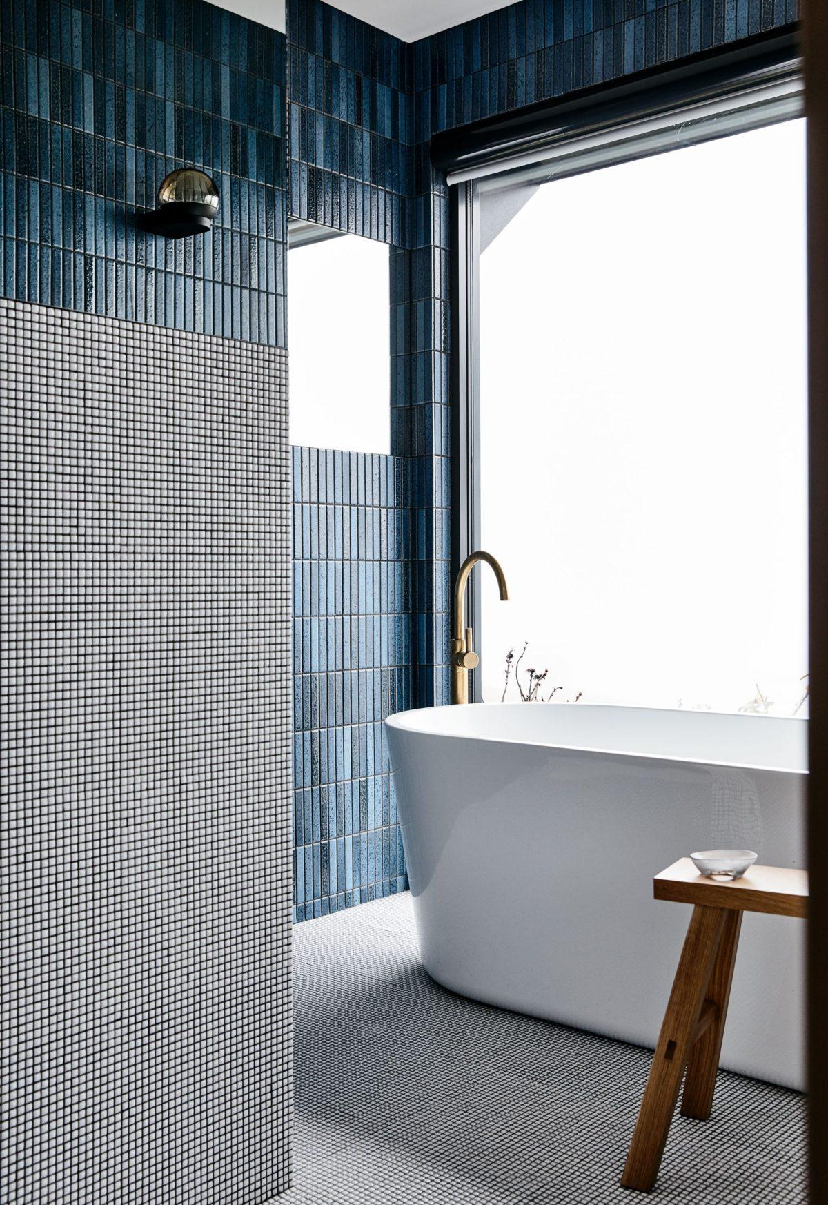 precioso baño decorado en azul, blanco y gris con azulejos de diseño, formas geométricas