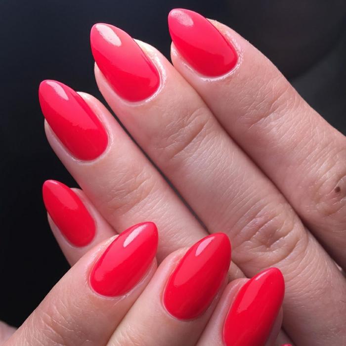 uñas pintadas en rojo acabado brillante, uñas con puntas afiladas forma afilada pintadas en rojo