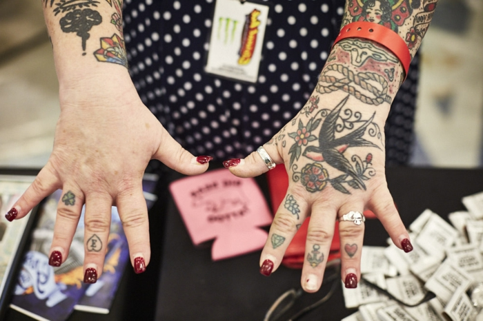 manos y brazos tatuados, símbolos típicos de los tatuajes tradicionales americanos, rosa de los vientos tatuaje, rosas, golondrinas
