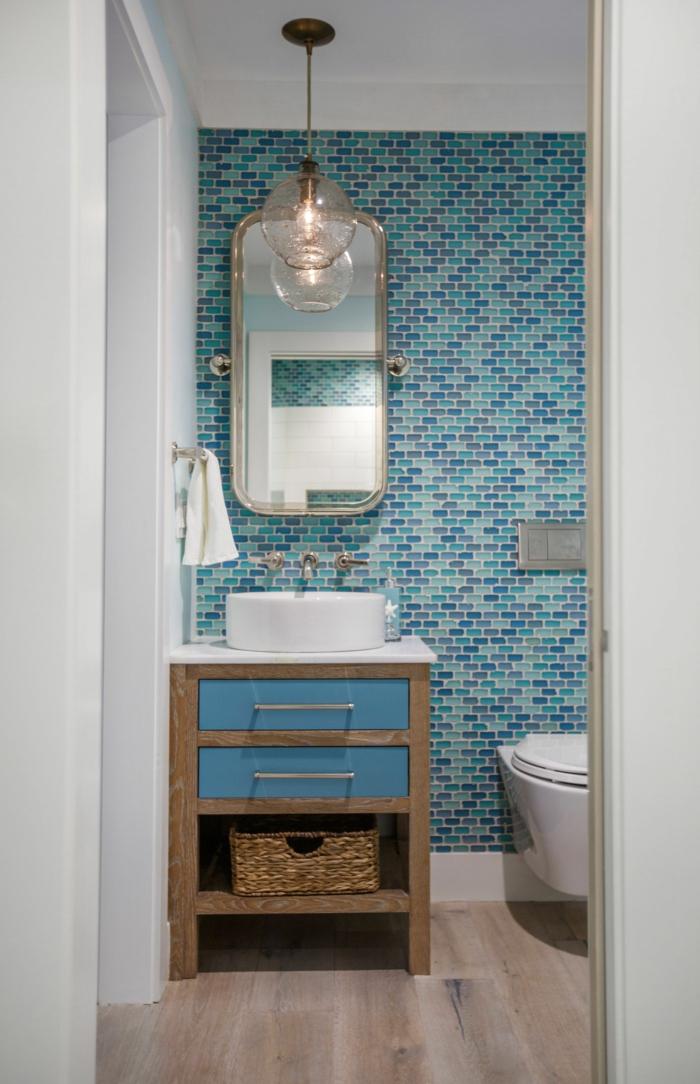 pequeño baño decorado en estilo vintage, paredes con azulejos en azul, muebles de madera y mimbre