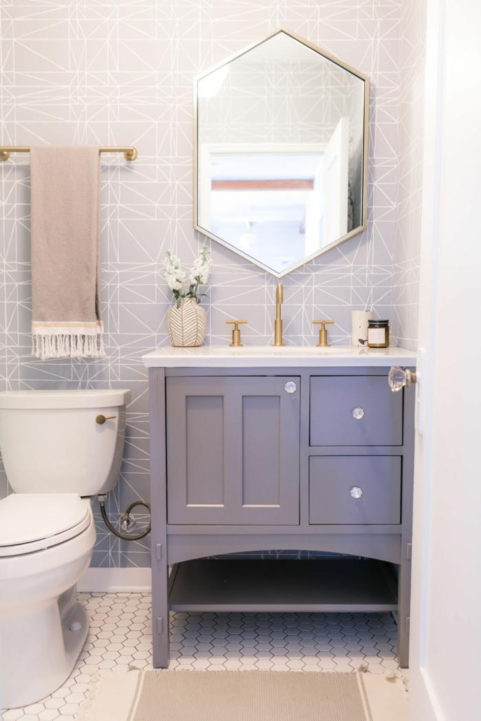 pequeño baño decorado en tonos pastel, paredes en gris con azulejos de diseño, detalles en rosado, espejo y azulejos de forma hexagonal