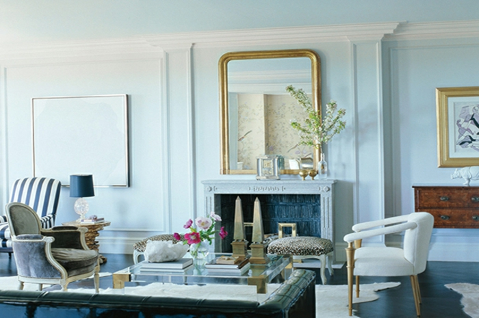 salón con paredes pintadas en azul claro y decoración en estilo vintage, sillones de diseño, elementos en dorado
