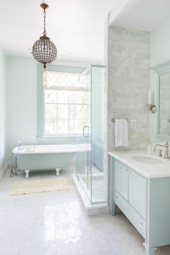 precioso baño decorado en blanco, gris claro y azul bebé, bañera patas garra y lámpara en estilo vintage