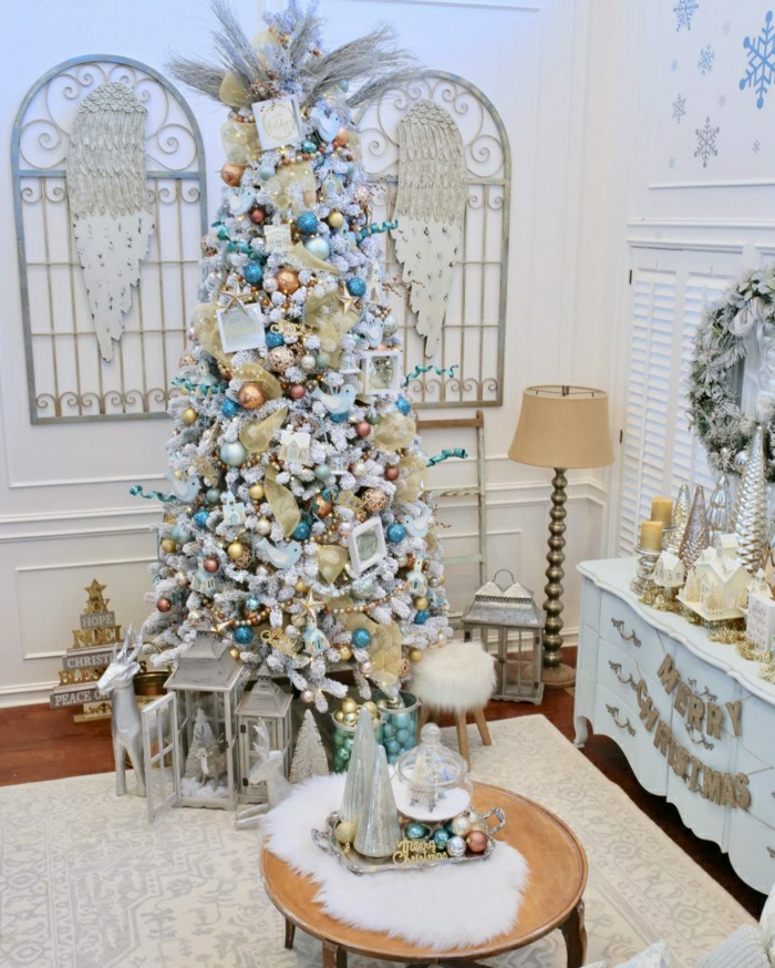 precioso árbol artificial con efecto de nevado decorado en tonos fríos, dormitorio juvenil en blanco