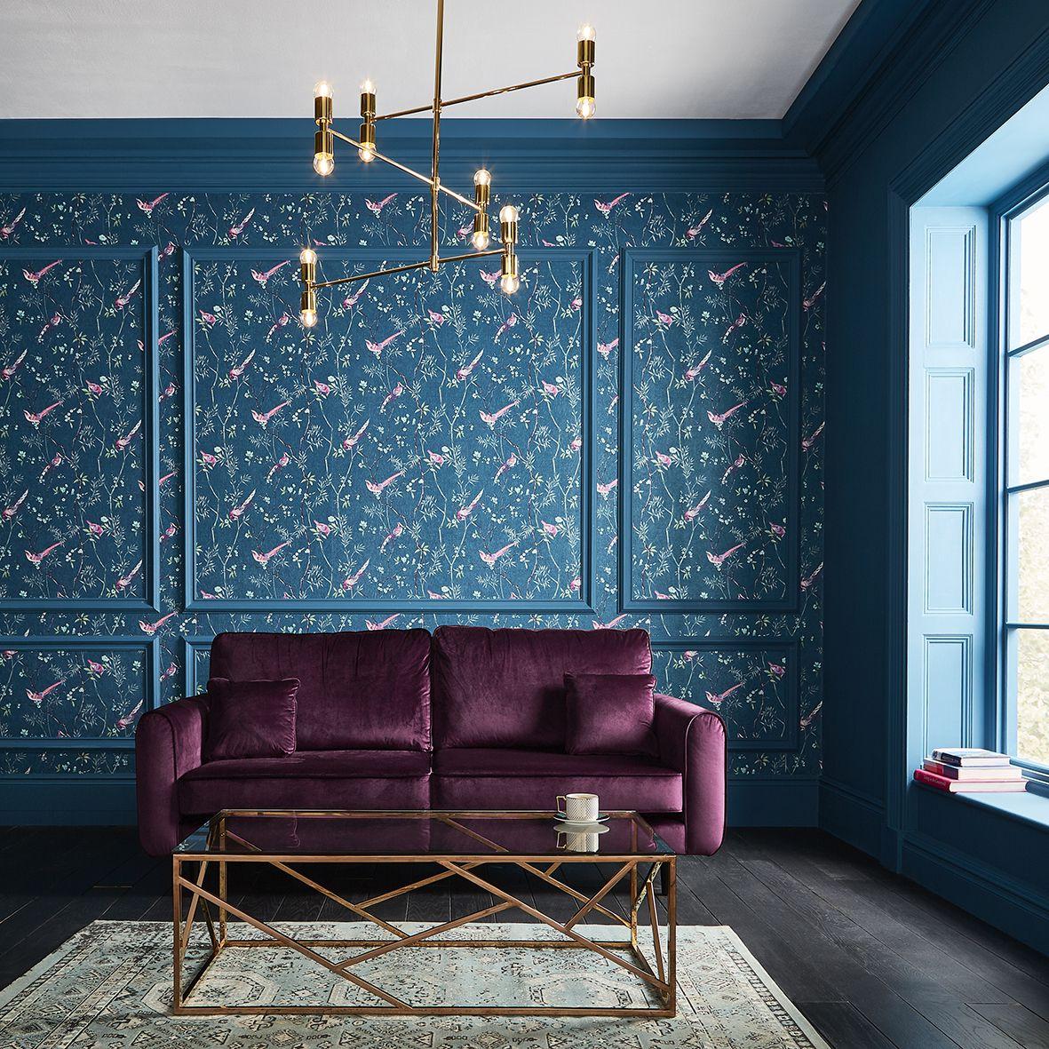 salón de diseño con toque vintage, qué colores se llevan para pintar un salón, sofá de terciopelo en morado, paredes pintadas en azul, papel pintado motivos florales