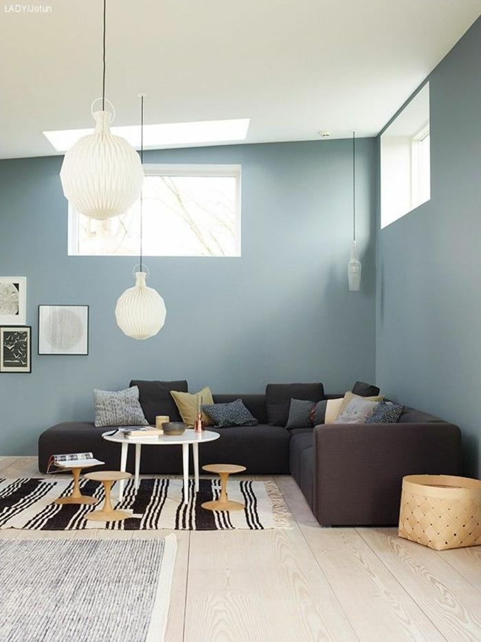 precioso salón con paredes pintadas en color azul porcelana, pared de madera, sofá grande en color gris oscuro