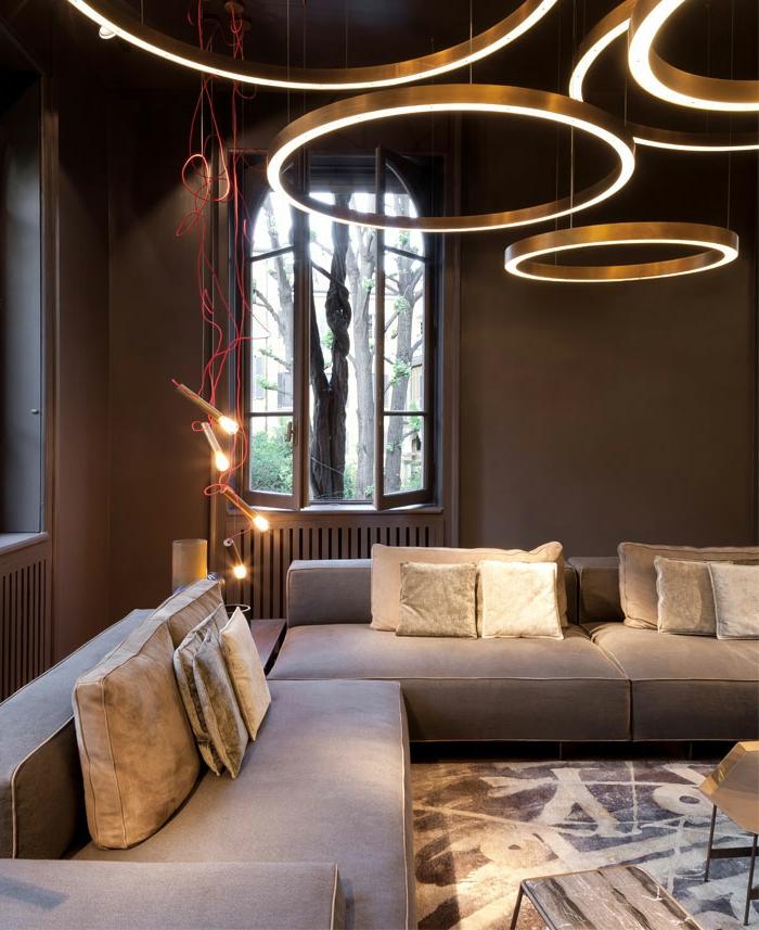 salón moderno decorado en colores terrestres y oscuros, paredes pintadas en marrón, cojines decorativos