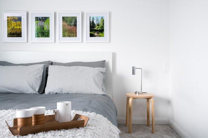cómo decorar un dormitorio gris y blanco, parares blancas decoradas con cuadros, sábanas grises, muebles de madera