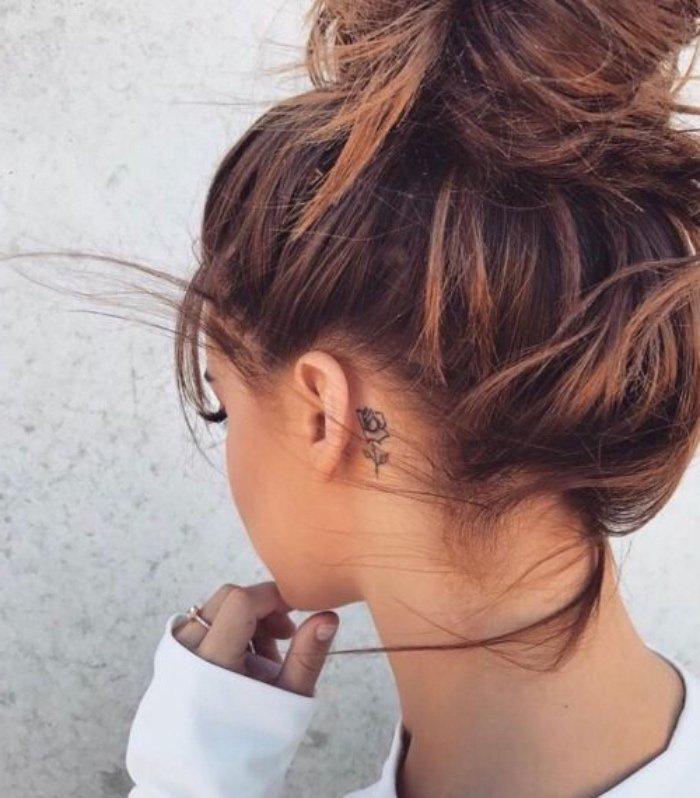 imágines de tattoos pequeños detrás de la oreja, pequeña rosa de diseño geométrico, mujer con pelo recogido en moño alto