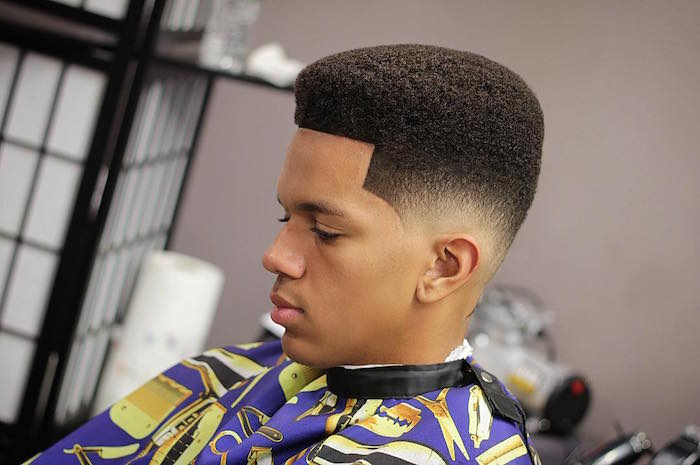 ideas de peinados degradado hombre, corte de pelo afro color oscuro con sienes rapados y tupe largo