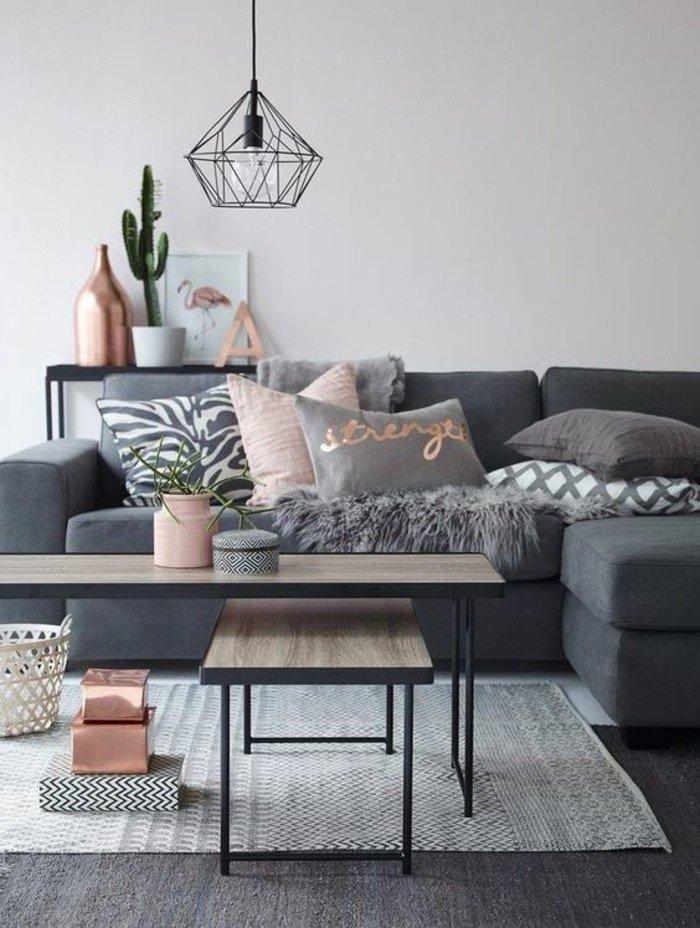 salón acogedor con paredes grises, sofá en gris oscuro, detalles decorativos en dorado y