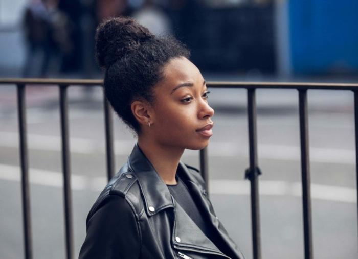 peinados pelo rizado fáciles y rápidos, pelo recogido en moño alto, mujer con chaqueta negra de cuero