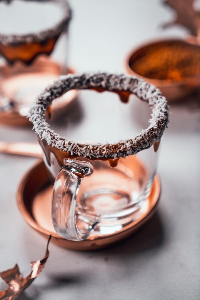 taza de vidrio transparente con bordes decorados con chocolate derretido y ralladura de coco, bebidas calientes caseras