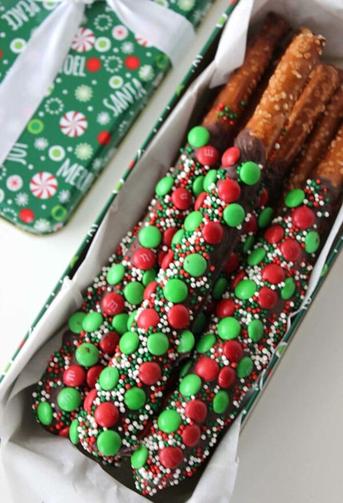 palitos de chocolate hechos con pretzels y chocolate adornados de caramelos en verde y rojo