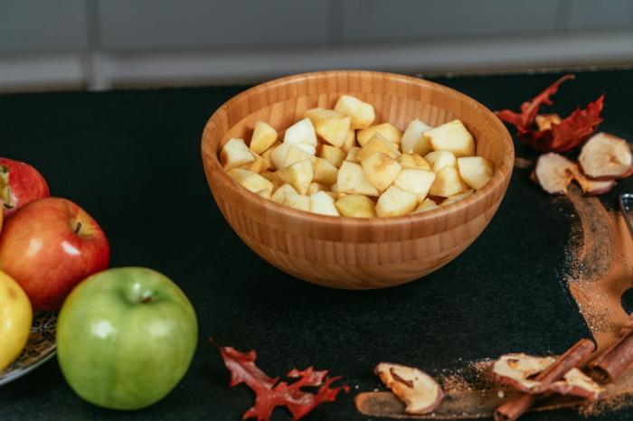trozos de manzana para hacer el relleno de la tarta, tarta con manzanas, vainilla, maicena, caramelo derretido, masa de harina y manteca