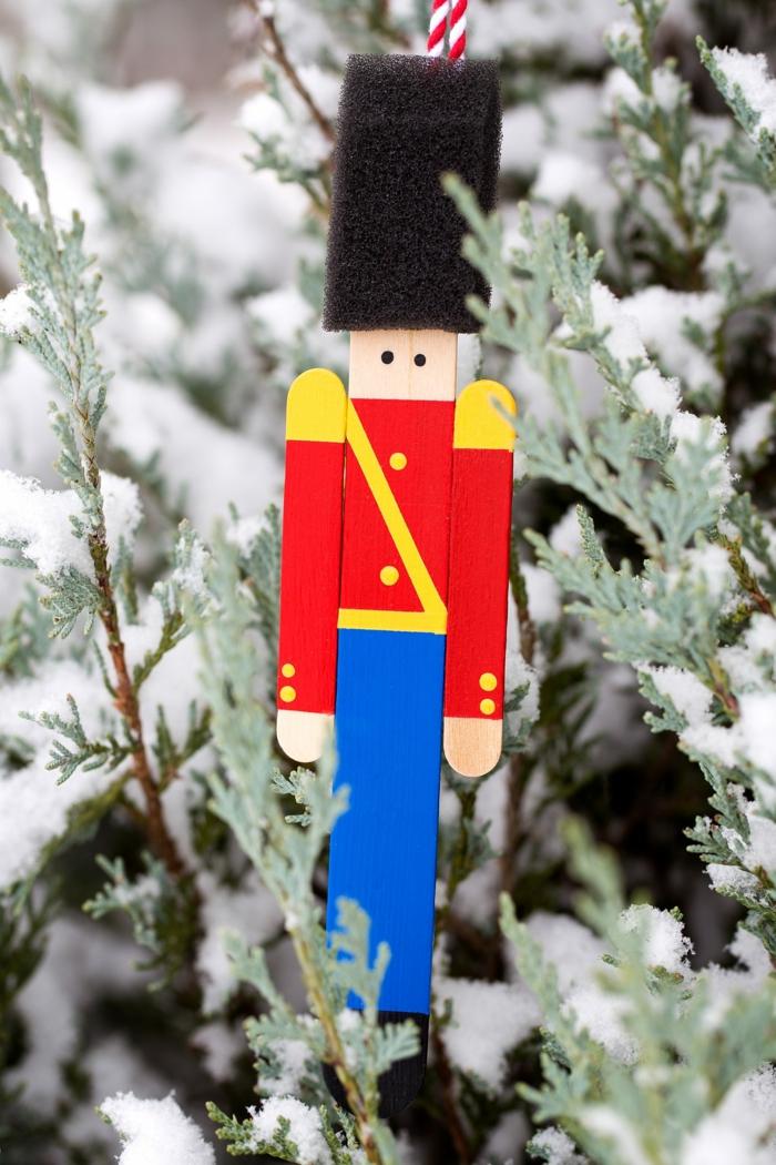 ideas de adornos navideños reciclados, soldadito de plomo hecho de materiales reciclados, palitos de madera pintados con pintura acrílica