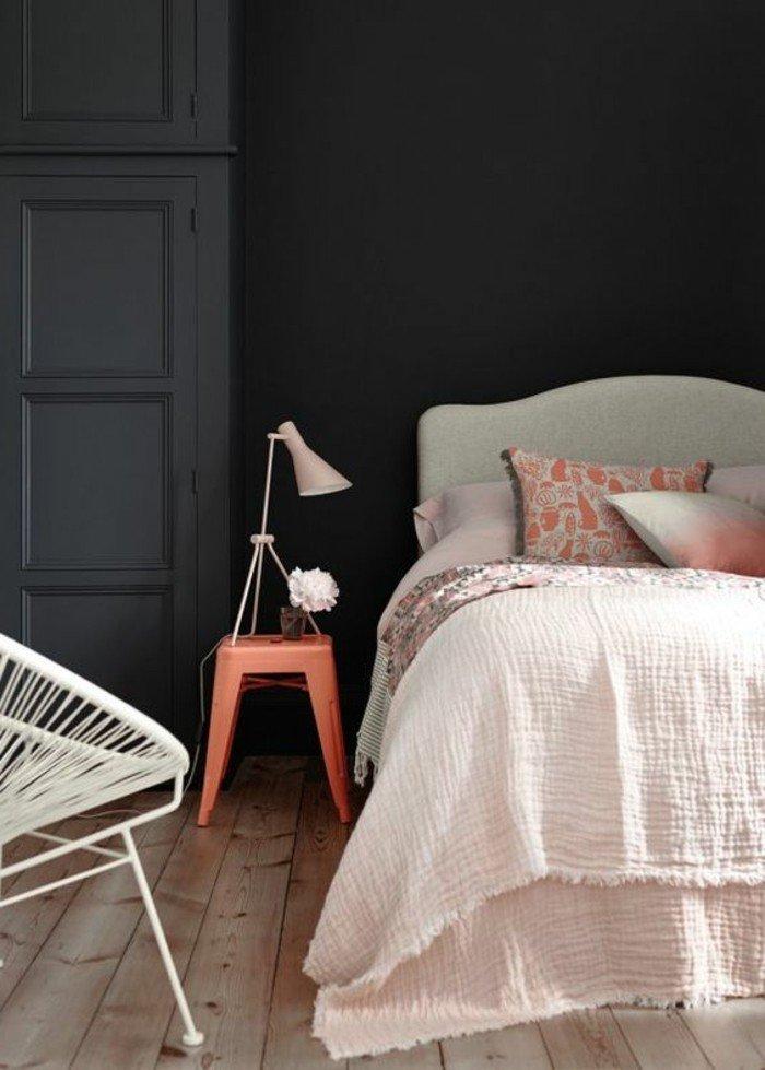 dormitorio decorado en colores pastel, sábanas en rosado, suelo de madera, paredes grises y puerta gris marengo