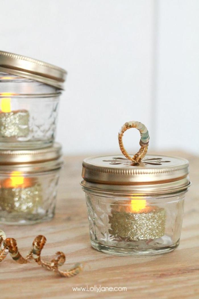 detalles caseros para decorar un arbol de navidad casero, botes de cristal decorados con luces dentro