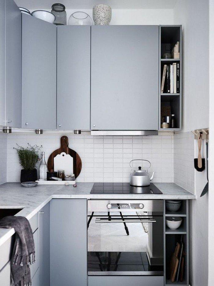 cocina decorada en color gris perla, armarios grises, encimera de marmol, azulejos blancos de forma rectangular