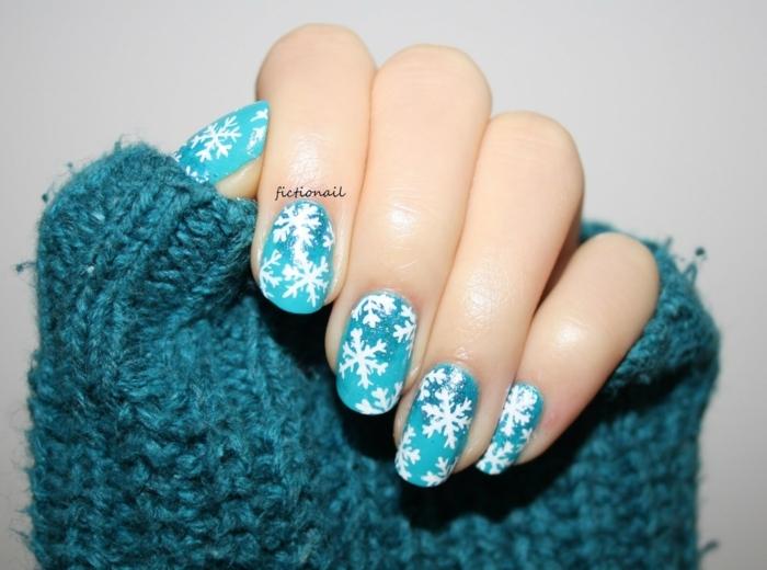 manicura bonita, uñas pintadas en azul claro con decoración en blanco, dibujos uñas de copos de nieve
