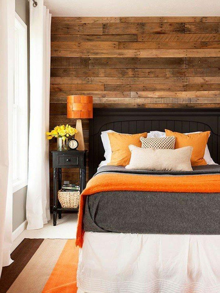 dormitorio acogedor con pared de madea decorado en gris y color naranja, cama negra con cabecero