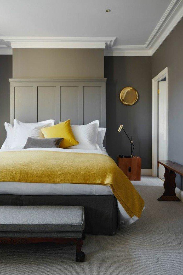 dormitorio matrimonio decorado en gris y amarillo con paredes grises, suelo de moqueta en gris, pie de cama