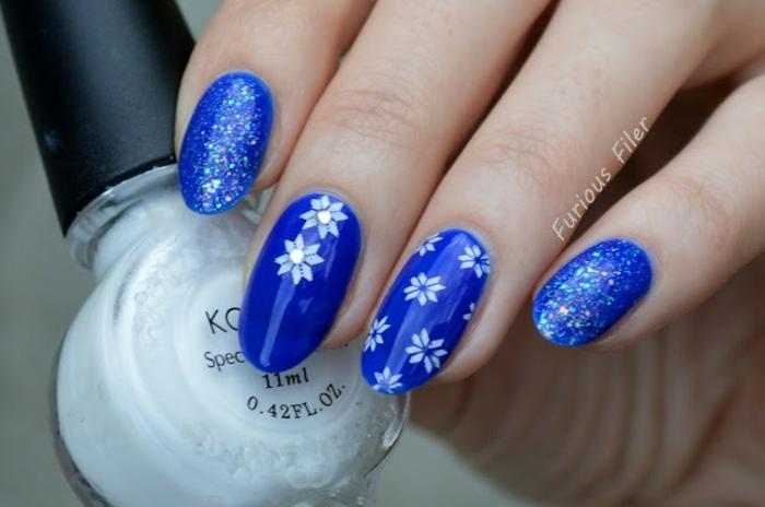 uñas de gel decoradas de forma almendrada pintadas en azul con decoraciones, dibujo de copos de nieve