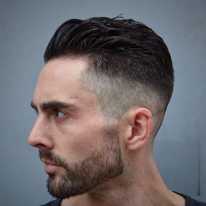 cabello negro con degradado, sienes rapadas y parte central larga, barba y bigotes ligeros