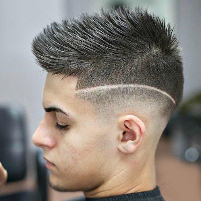 degradado pelo hombre con cabello texturizado hacia arriba y mucho volumen, raya lateral y sienes rapadas
