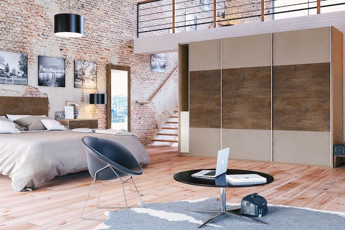 dormitorio abierto al salón decorado en estilo industrial, alfombra gris marengo, paredes de ladrillo