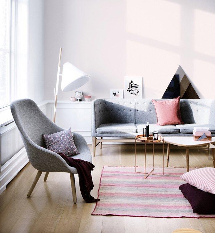 salón decorado en tonos pastel, muebles de diseño en gris marengo, paredes en rosado, suelo de parquet