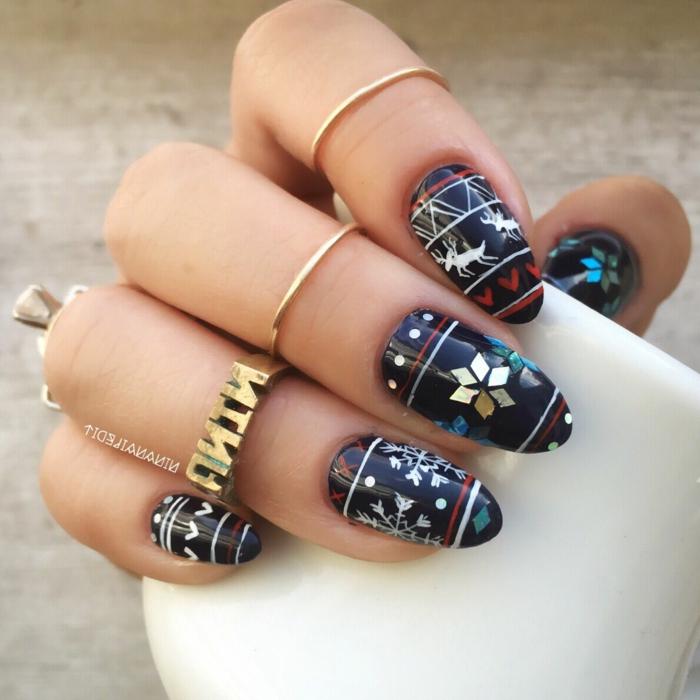 cuáles son las uñas de navidad más bonitas, uñas largas almendradas pintadas en azul oscuro con dibujos