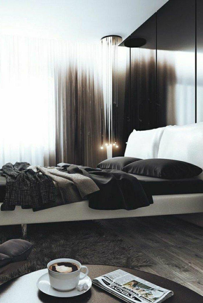 dormitorio gris y blanco de diseño, pared en negro, cama doble en blanco, suelo de madera, mesa oval