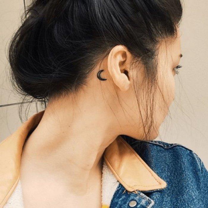 tatuajes chiquitos detrás de la oreja, pequeño detalle en negro, tatuaje de luna en estilo minimalista