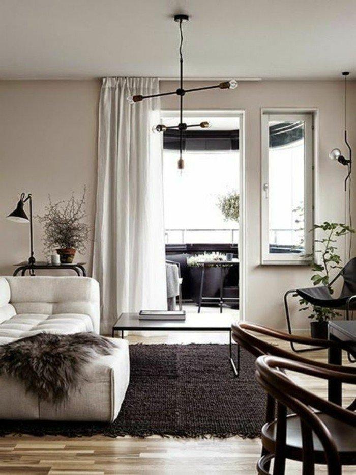 espacio decorado en color gris perla, suelo de madera con alfombra en gris oscuro, sofá blanca y cortinas blancas