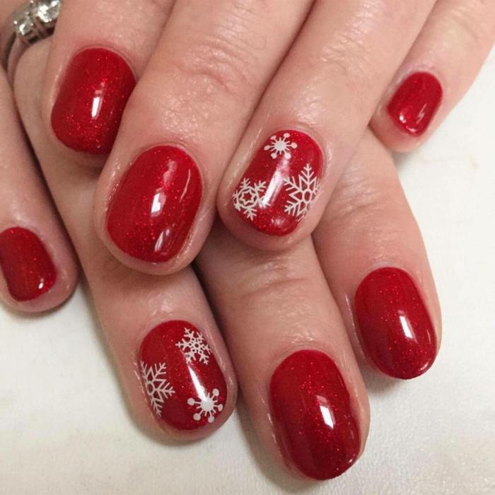 uñas cortas pintadas en rojo brillante con partículas relucientes y pequeños detalles en blanco, dibujos de copos de nieve
