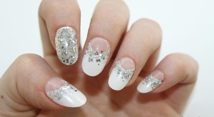 preciosa manicura con media luna, uñas pintadas en blanco con partículas relucientes en plateado