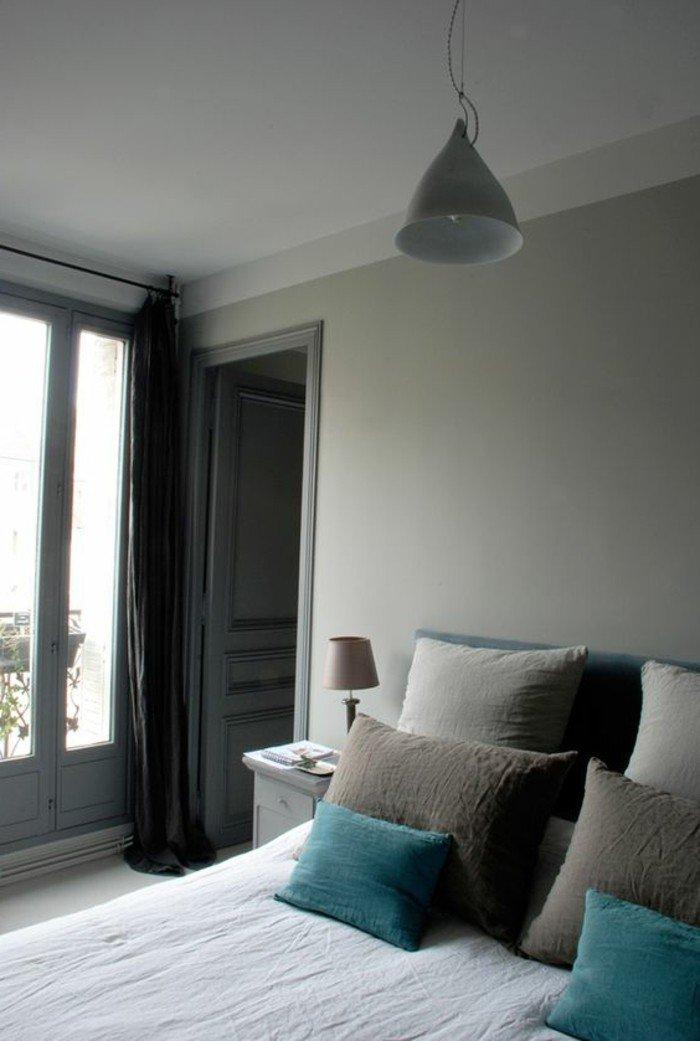 habitación decorada en gris perla, cojines decorativos en gris y verde, cortinas negras, dormitorio en estilo minimalista