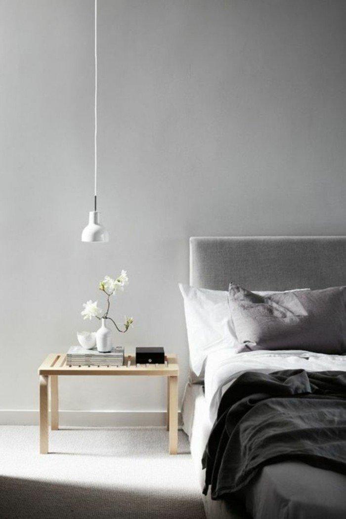 precioso dormitorio gris y blanco decorado en estilo escandinavo, mesita de noche de madera, cama con cabecero