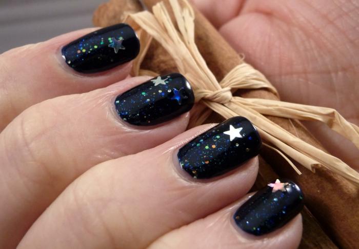 uñas largas de forma cuadrada pintadas en negro con partículas relucientes y pegatinas en forma de estrella